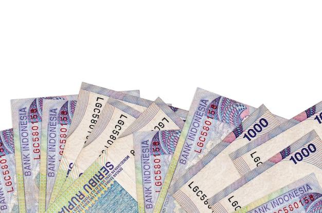 Банкноты 1000 индонезийских рупий лежат в нижней части экрана, изолированы на белом фоне с копией пространства