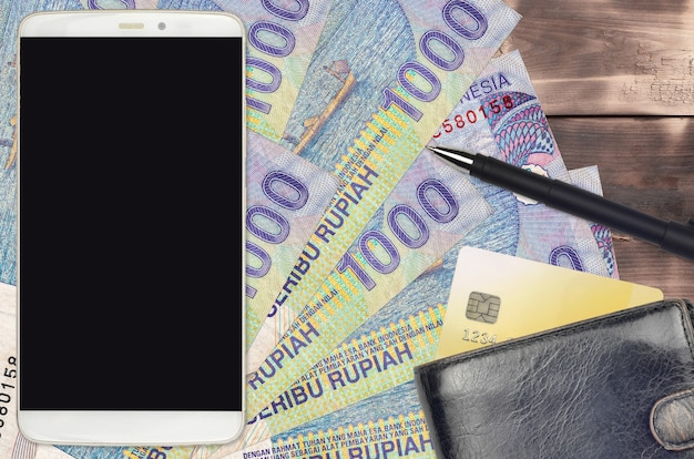 1000 indonesian rupiah bills and smartphone with purse and credit card