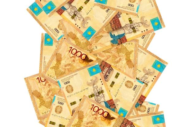 1000カザフスタンテンゲ手形が白で隔離されて飛んでいます。多くの紙幣が左右に白いコピースペースで落ちています