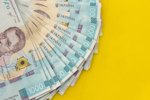 黄青色の背景にウクライナの1000の新しい紙幣。節約とお金の概念。ウクライナのお金。