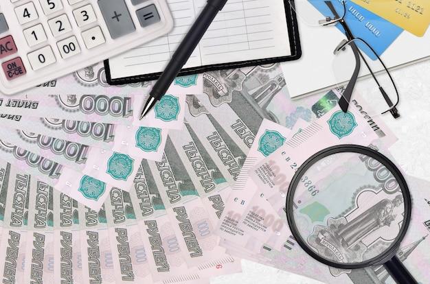 Купюры 1000 российских рублей и калькулятор с очками и ручкой. концепция сезона уплаты налогов или инвестиционные решения. ищу работу с высокой зарплатой