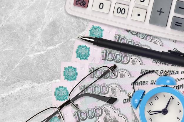 Купюры 1000 российских рублей и калькулятор с очками и ручкой.