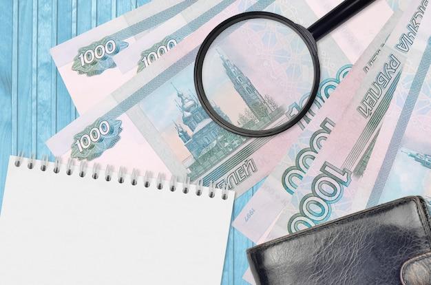 Купюры 1000 российских рублей и увеличительное стекло с черным кошельком и блокнотом. понятие о поддельных деньгах. поиск различий в деталях денежных купюр для обнаружения фальшивых денег