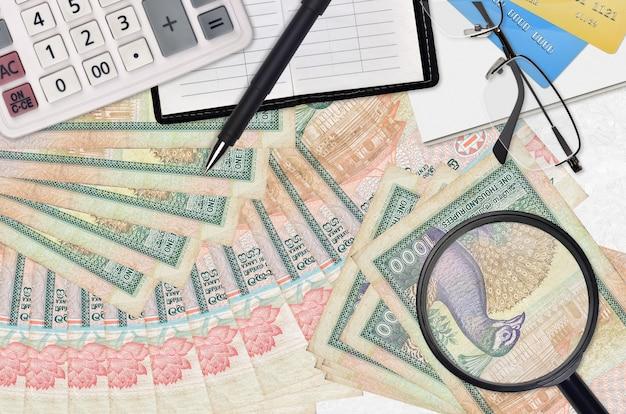 1000スリランカルピー紙幣とメガネとペン付き電卓