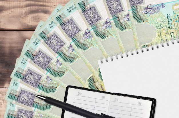 1000 sri lankan rupees bills fan and notepad with contact book and black pen.
