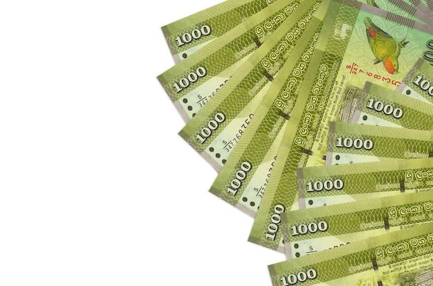 1000スリランカルピー紙幣はコピースペースのある白い壁に隔離されています。豊かな生活の概念的な壁。大量の自国通貨の富