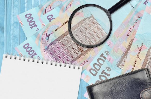 Купюры 1000 украинских гривен и увеличительное стекло с черным кошельком и блокнотом. понятие о поддельных деньгах. поиск различий в деталях денежных купюр для обнаружения фальшивых денег