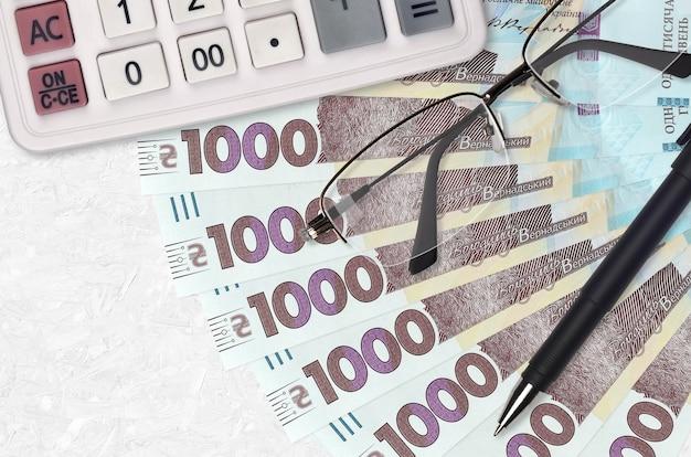 Вентилятор банкнот 1000 украинских гривен и калькулятор с очками и ручкой.