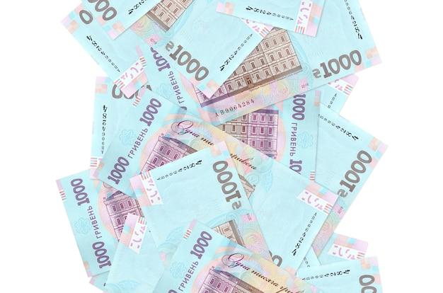 1000のウクライナグリブナの請求書が白で隔離されて飛んでいます。多くの紙幣が左右に白いコピースペースで落ちています