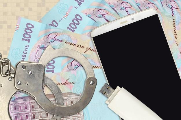 1000 ukrainian hryvnias bills and smartphone with police handcuffs.