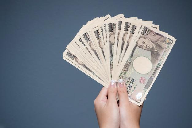日本円10000ノートを持っている女性の手を閉じる