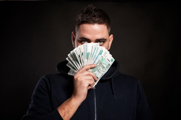 Молодой брюнетный мужчина держит купюру в 1000 рублей с веером на лице и смотрит