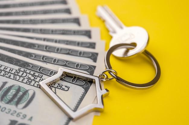 黄色の背景に100米ドルのパックの上に横たわる金属製のキーを持つ家の形をした金属製キーチェーン