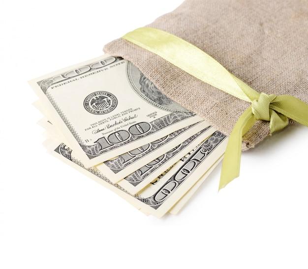 白で隔離の袋に100ドル札のスタック。
