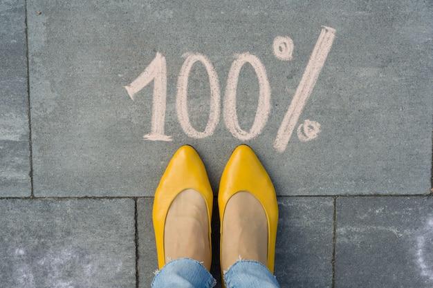 Женские ноги с текстом 100 процентов написано на сером тротуаре.