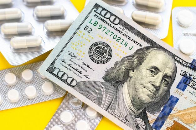 Крупным планом 100 долларов сша и много таблеток на желтом