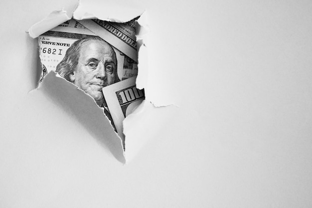 穴の開いた紙の下で100ドルの請求書
