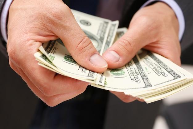 男は100ドル札の腕のパックを保持します。