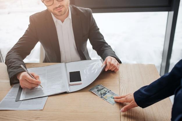 Счет касания руки женщины 100 долларов на таблице в комнате. она отдаёт это мужчине. он пишет в тетради и смотрит на деньги. вырезать вид.