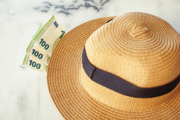 Шляпа солнца с банкнотами 100 сотых евро. концепция отдыха