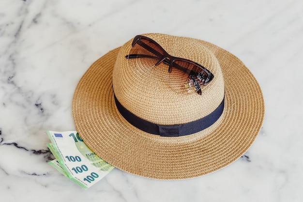 Шляпа от солнца с солнцезащитные очки и банкноты 100 сотых евро. концепция отдыха