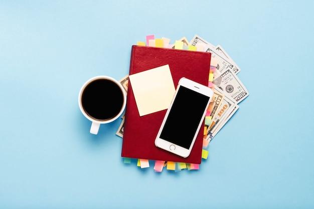 ページ上のステッカー、赤いコーヒーカップ、100ドル、白い電話、青い背景の赤い日記。成功するビジネス、適切な計画、時間管理の概念。フラット横たわっていた、トップビュー