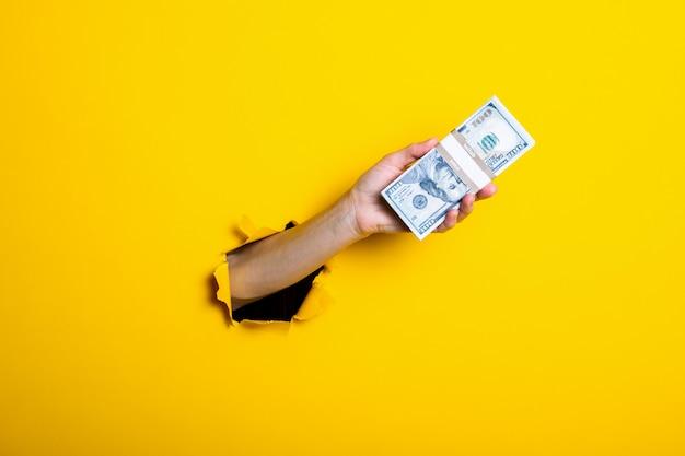 女性の手は100ドル札の束を保持しています。