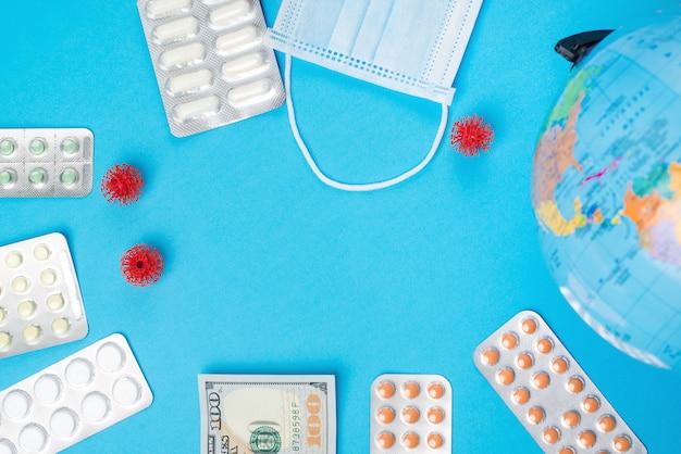 Мировая вспышка коронавируса. 100 долларов, пилюльки и лицевой щиток гермошлема на голубой предпосылке, взгляд сверху. копировать пространство коронавирус распространился по миру.