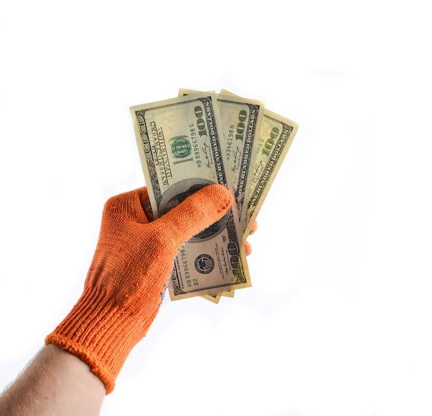 オレンジ色の作業用手袋をした男性の手は、100ドル札を持ち、仕事と給料の支払いをします。白で隔離