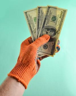オレンジ色の作業用手袋をした男性の手は、100ドル札を持ち、仕事と給料の支払いをします。