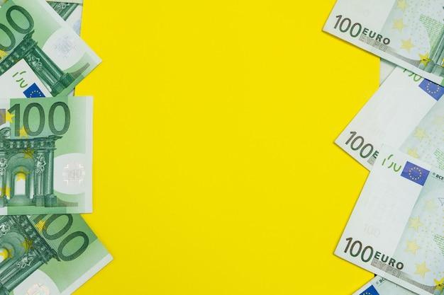 黄色のコピースペースを持つ100ユーロの多くの紙幣、欧州通貨背景フラットレイアウト