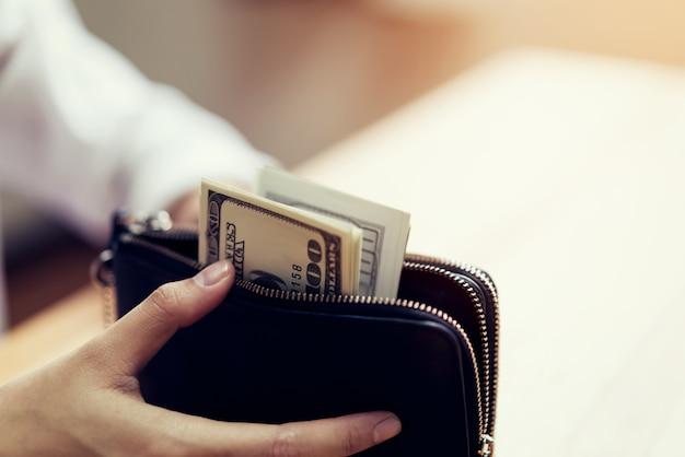 手、財布に100ドル紙幣を持っています。現金による支出の概念。