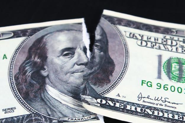 破れた切り下げられた100ドル紙幣。ドルの崩壊。切り下げ。下落通貨
