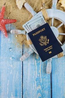 船乗りのキャプテンホイールで、100ドル札以上の砂浜で貝殻のコンセプトを旅行するアメリカンパスポート
