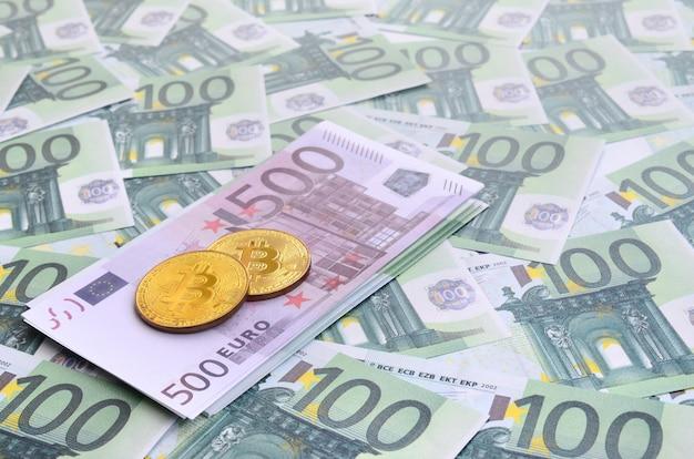 黄金の物理的なビットコインは100ユーロの緑の通貨単位のセットにあります。たくさんのお金が無限のヒープを形成します