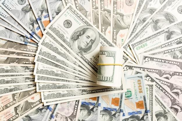 Закройте вверх кучи 100 долларовых банкнот на предпосылке сделанной с различными банкнотами доллара. вид сверху финансового