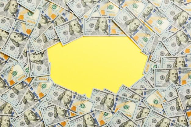 100ドル札のフレーム。黄色の背景にビジネスコンセプトのトップビュー