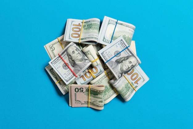 青に分離された100ドル札の多くのスタック