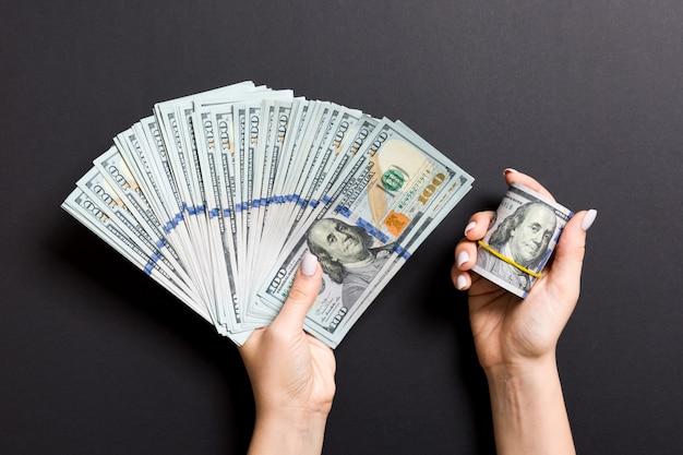 100ドルのファンを持っている女性の手の平面図です。ローンのコンセプト。繁栄の概念