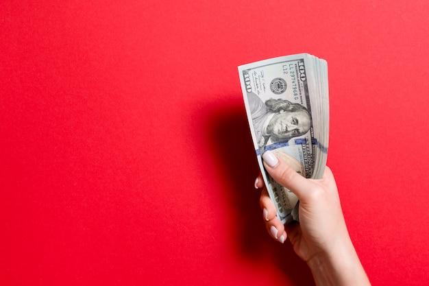 女性の手で100ドル紙幣の束。コピースペースと金融とビジネスのコンセプト