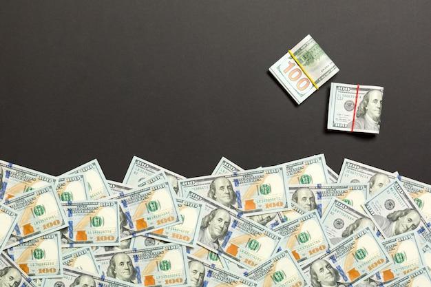 テキストビジネスお金の概念のための空の場所で、色付きの背景平面図上のアメリカのお金。現金のスタックで100ドル札