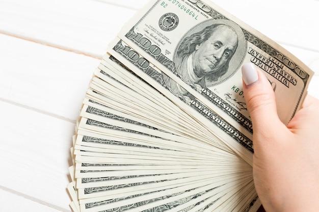 木製のお金のファンを持っている女性の手の斜視図。 100ドル札。信用と債務