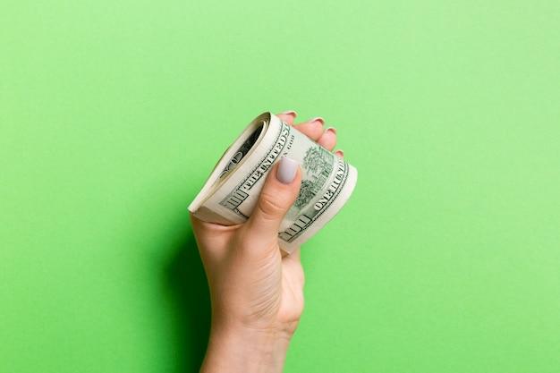 カラフルな背景に女性の手で100ドル札のパック。給与コンセプト