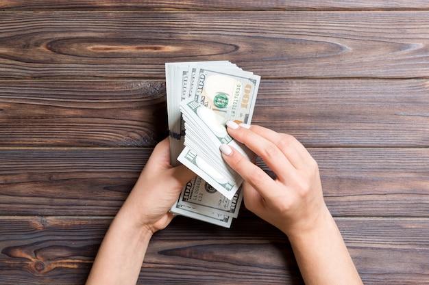 木製の背景に100ドル紙幣を数える実業家の手の平面図