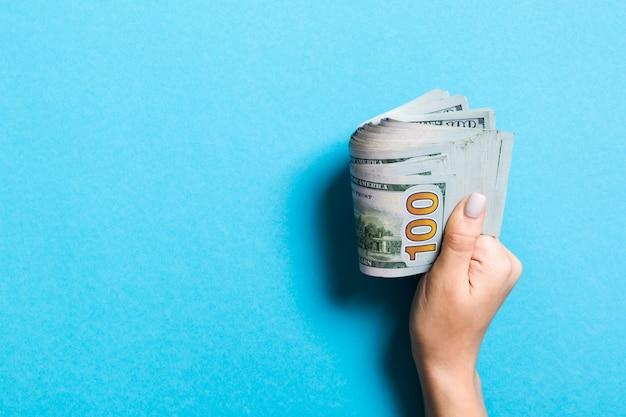 お金の束をしっかりと保持している女性の手。カラフルな100ドルの平面図。コピースペースの投資コンセプト