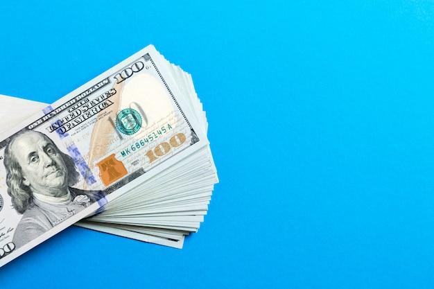 Стог банкнот 100 долларов на красочной предпосылке. вид сверху финансовой концепции с пустым пространством для вашего дизайна