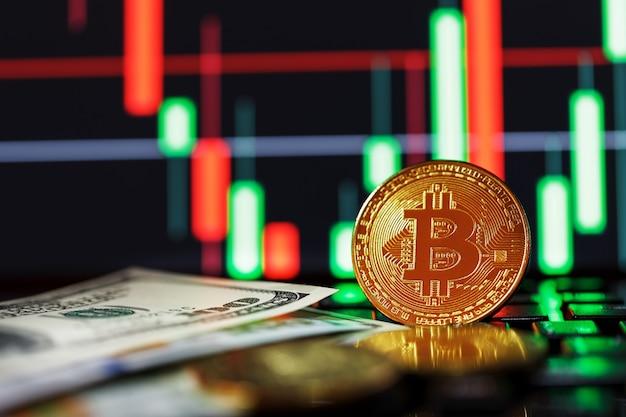 Золотые биткойны на фоне бизнес карт крупным планом и 100 долларовых купюр.