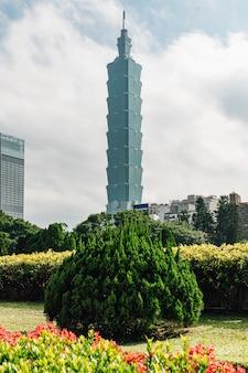 Здание тайбэя 101 с кустами дерева на переднем плане.