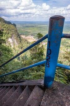 끄라비(krabi) 주에 있는 호랑이 동굴 사원(tiger cave temple)의 높은 계단에 있는 1028개의 계단. 콘크리트 계단과 철제 난간. 바위와 필드의 거리 보기입니다.