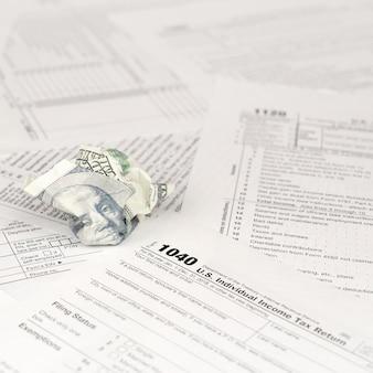 1040個人所得税申告書と100ドル札をくしゃくしゃ